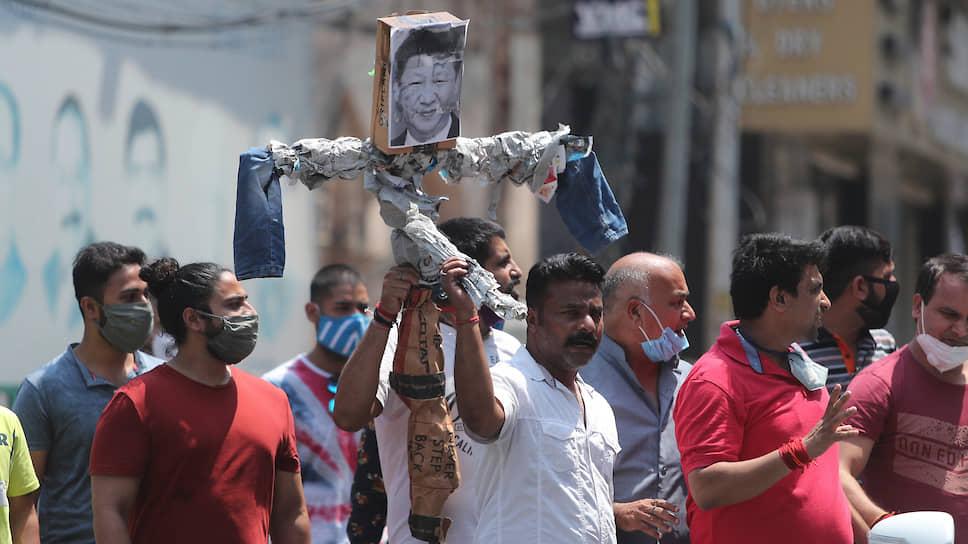 Индийцы держат портрет лидера Китая Си Цзиньпина во время протеста против действий Китая в Восточном Ладакхе
