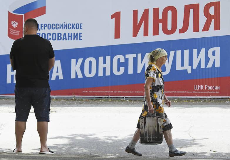 Москва. Прохожие на фоне плаката, посвященного всероссийскому голосованию по поправкам в Конституцию