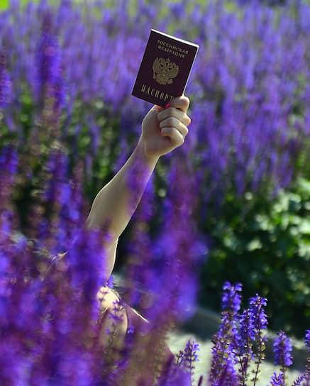 Россия. Девушка держит паспорт РФ среди цветов