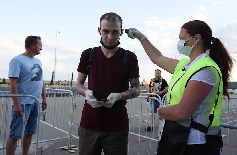 Сотрудница стадиона «Фишт» измеряет температуру у болельщика перед началом матча