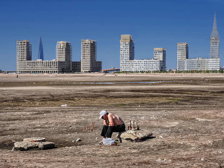 Санкт-Петербург, Россия. Мужчина сидит на камне около строящегося микрорайона