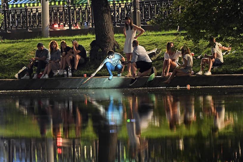 Отдыхающие около пруда в парке