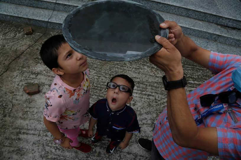 Непальские дети наблюдают солнечное затмение через темное стекло