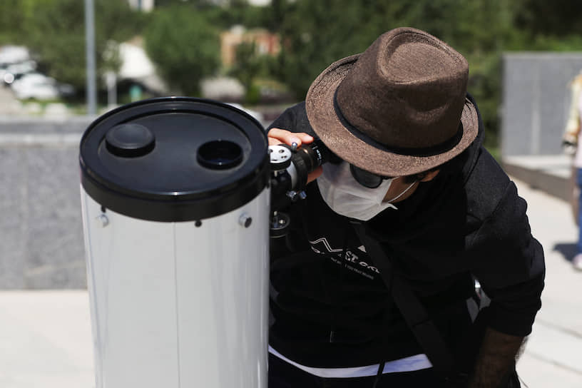 Мужчина наблюдает за затмением в Тегеране с помощью телескопа
