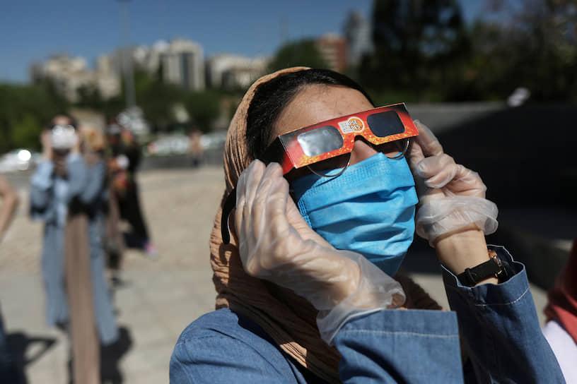 Женщина смотрит на затмение в Тегеране