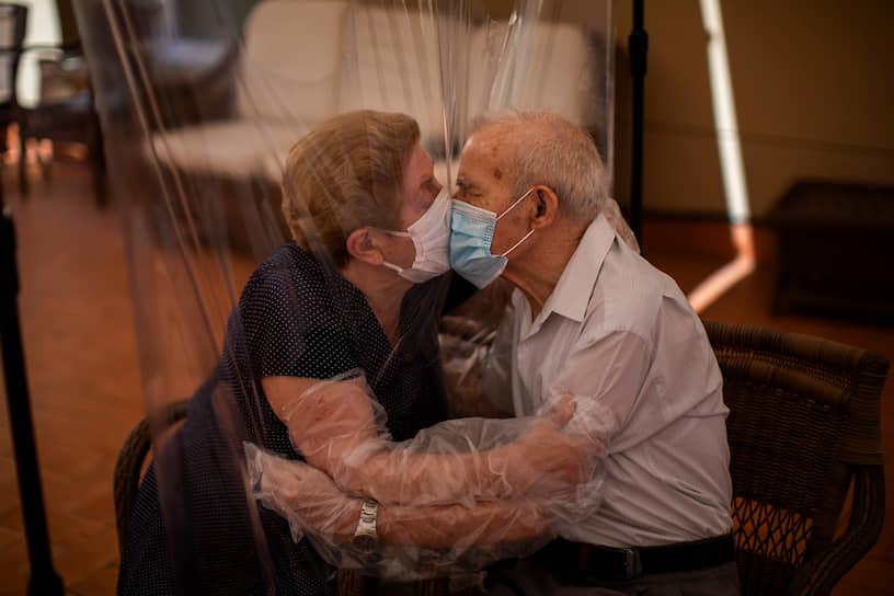 Барселона, Испания. Люди целуются через защитную пленку в доме престарелых