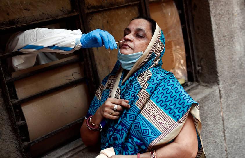 Нью-Дели, Индия. Медработник берет у женщины мазок на коронавирус