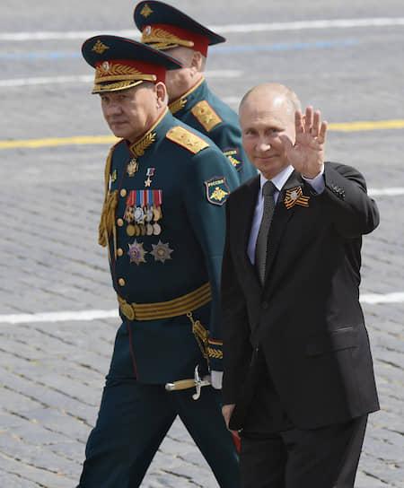 Министр обороны РФ Сергей Шойгу (в центре) и президент Владимир Путин после парада