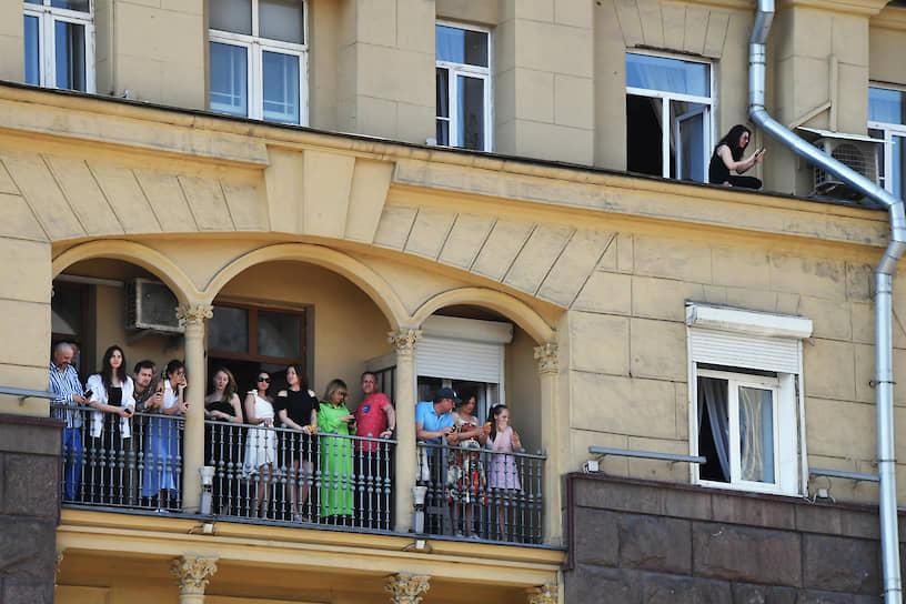 Зрители наблюдают с балконов за проходом военной техники по Москве