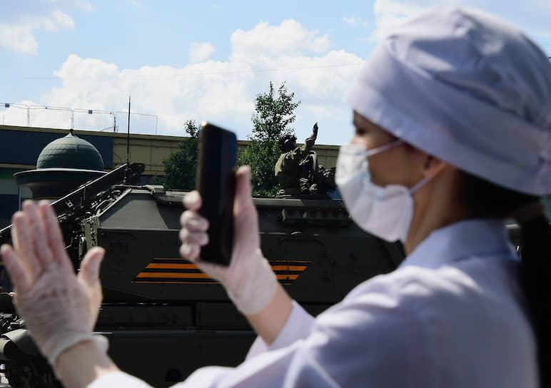 Девушка снимает на телефон проезд военной техники по улице Новый Арбат