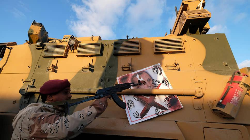 Член Ливийской национальной армии указывает на плакат с изображением президента Турции Реджепа Тайипа Эрдогана