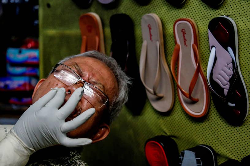 Джакарта, Индонезия. Медработник берет мазок на коронавирус у местного продавца