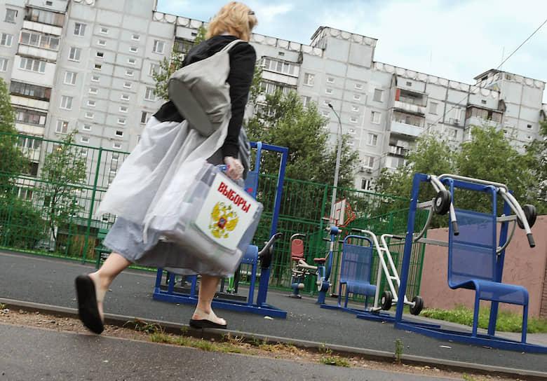 Член избирательной комиссии с урной в городе Королев Московской области