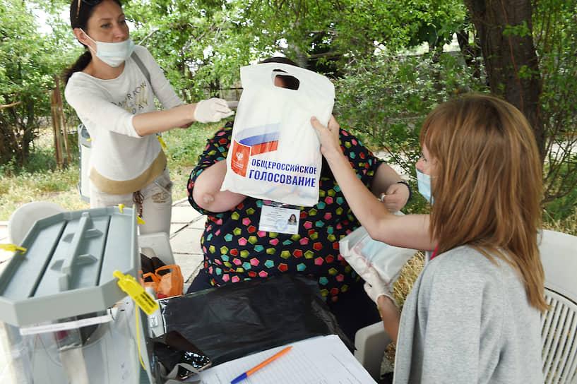 Сотрудники избиркома с пакетом для голосования в Ялте