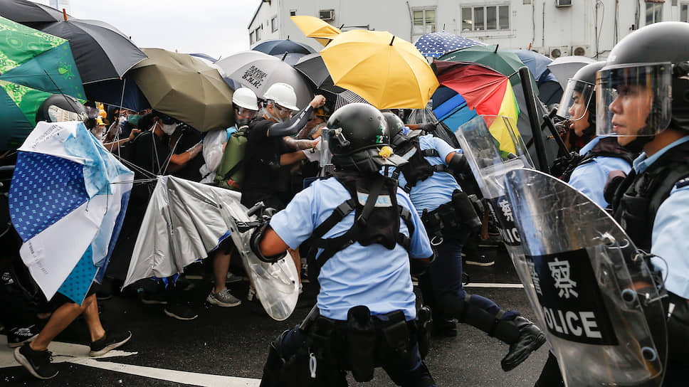 Полиция пытается разогнать протестующих возле места церемонии поднятия флага КНР, 2019 год