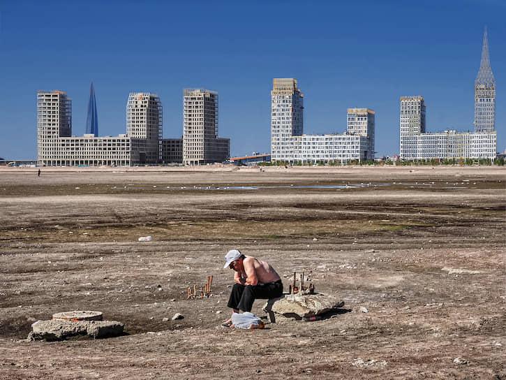 14 июня. Санкт-Петербург. Мужчина сидит на фоне строящегося микрорайона