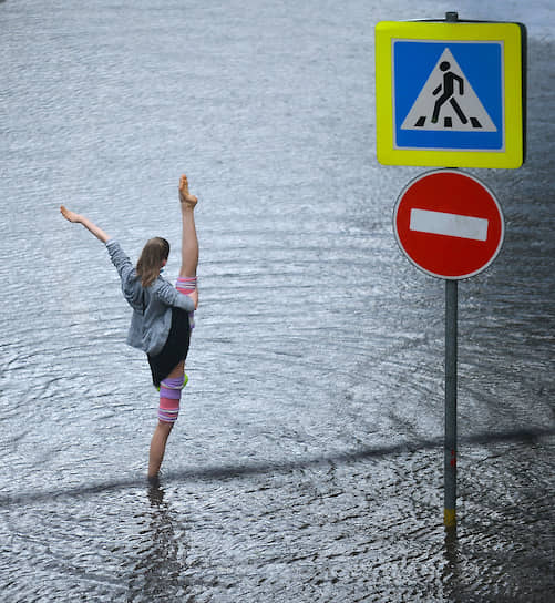 20 июня. Москва. Девушка стоит на затопленной проезжей части после проливного дождя