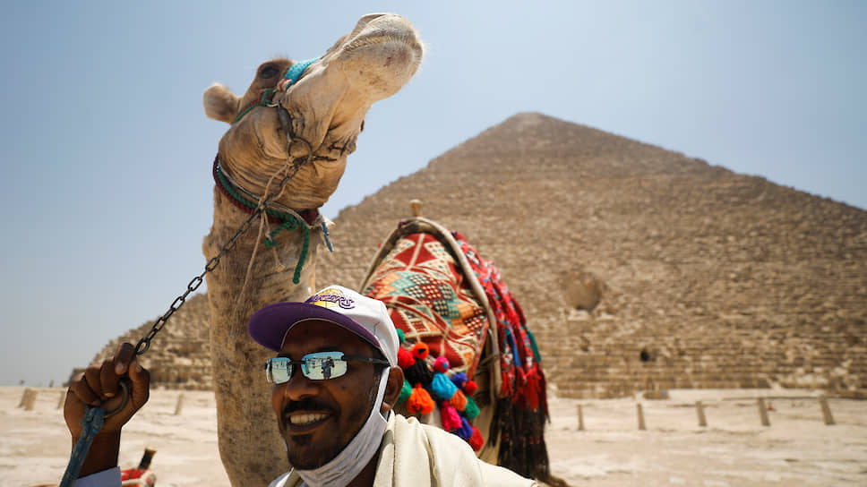 Каир, Египет. Мужчина с верблюдом на фоне пирамиды