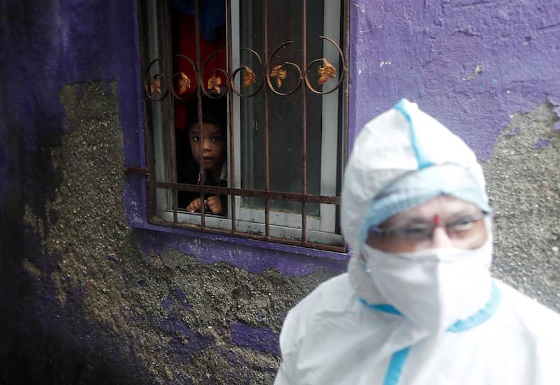 Мумбаи, Индия. Мальчик наблюдает за медработником