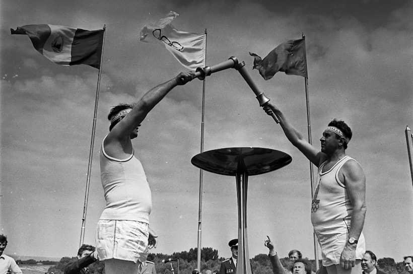 Всего в Играх участвовали 5,2 тыс. спортсменов из 80 государств — это было самое низкое количество стран-участниц на летних Олимпиадах с 1956 года <br>На фото: румынский борец Николае Мартинеску (слева) передает огонь советскому бегуну Петру Болотникову
