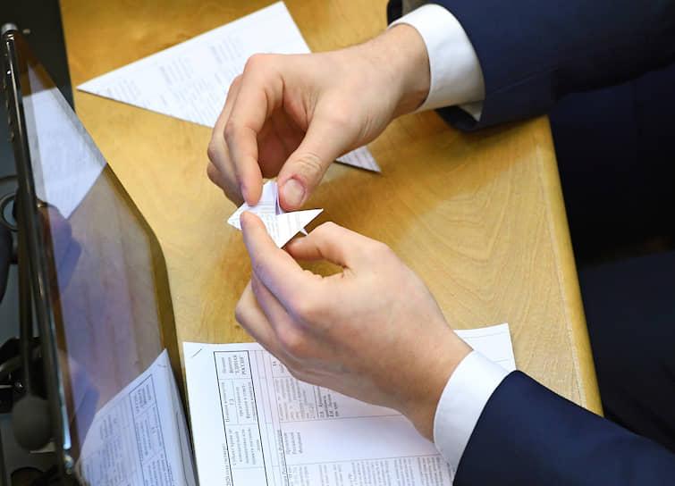 Депутат делает из бумаги оригами во время заседания