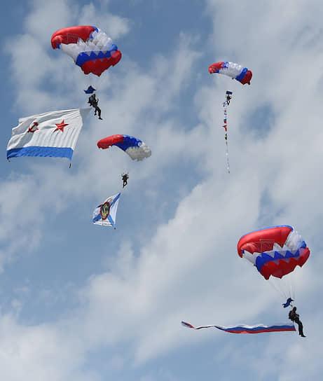 Парашютисты с флагами ВМФ и России в небе во время военно-морского парада в Севастопольской бухте
