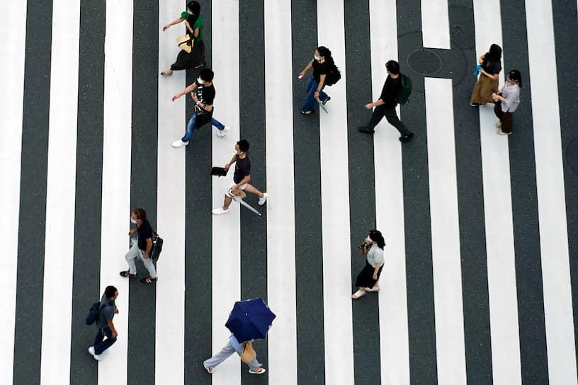 Токио, Япония. Люди в защитных масках на пешеходном переходе