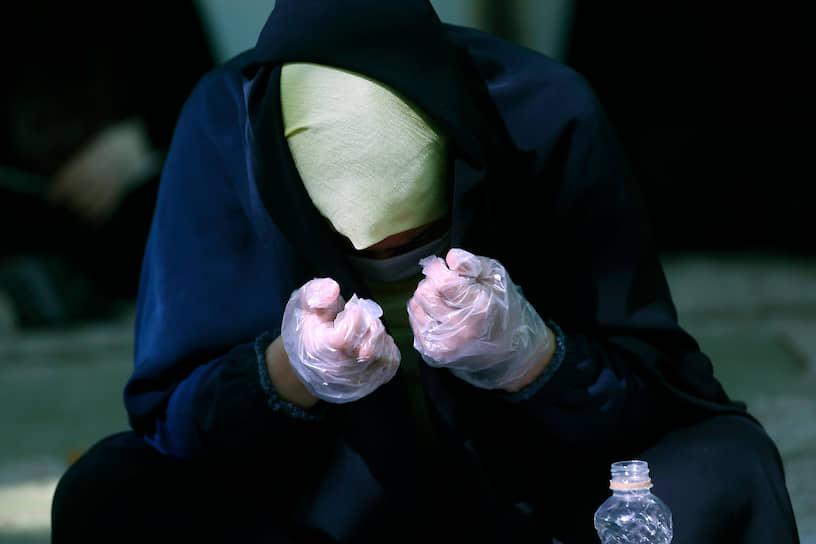 Тегеран, Иран. Женщина в защитной маске и перчатках во время молитвы