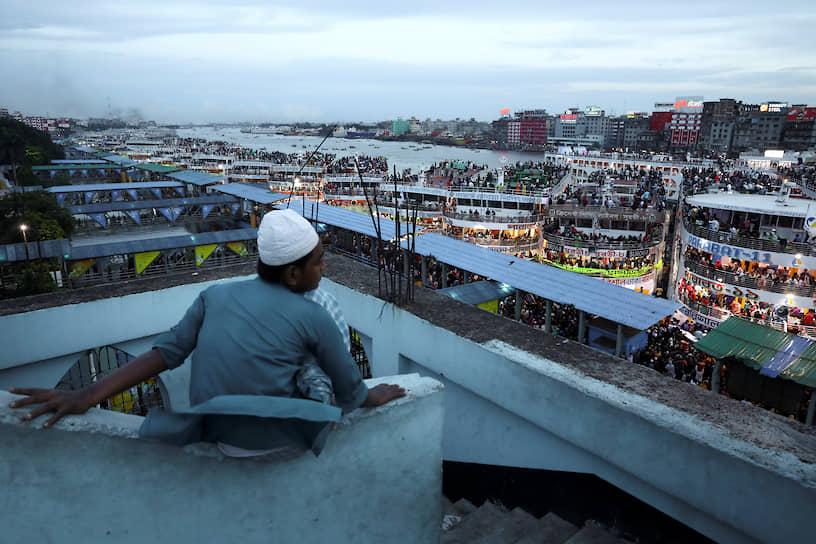 Дакка, Бангладеш. Мужчина наблюдает за людьми на паромах
