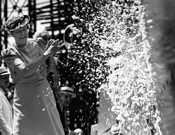 Перед спуском на воду нового корабля проводят специальный ритуал — о его борт разбивают бутылку шампанского<br> На фото: супруга президента США Элеонора Рузвельт разбивает бутылку шампанского о нос корабля S.S. America, 1939 год