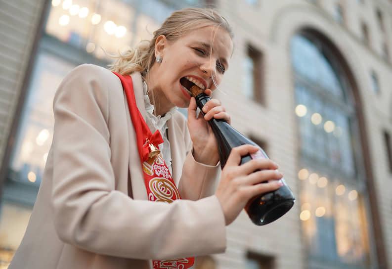 Выпускница открывает бутылку шампанского в день последнего звонка в школе