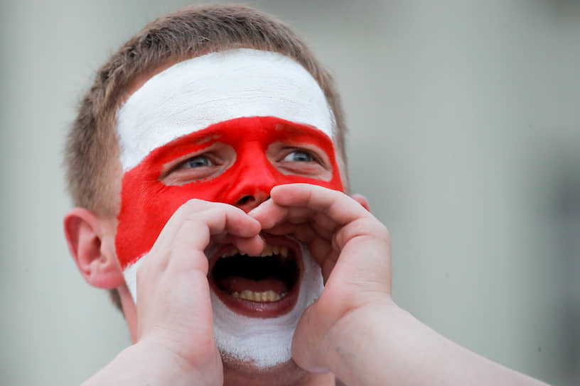 Участник акции протеста с красно-белым флагом на лице