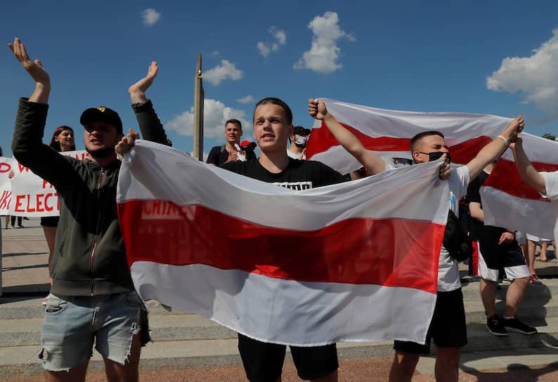Люди стоят у стелы «Минск — город-герой», а также на трех других сторонах перекрестка