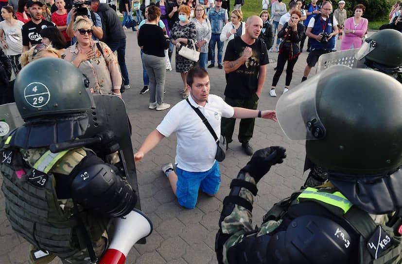 Участник акции стоит на коленях перед сотрудниками правоохранительных органов