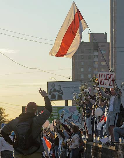 Участники акции в поддержку задержанных и пострадавших во время протестов 9 августа с флагом