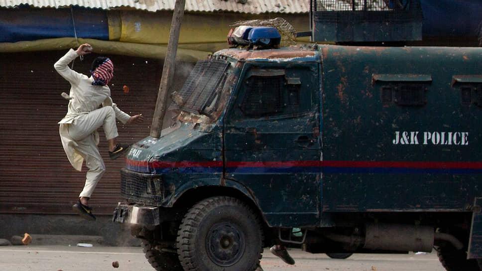 Протестующий нападает на полицейскую машину в Сринагаре (Кашмир)