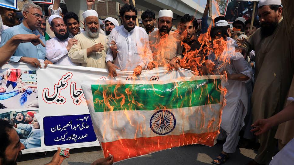 Участники акции солидарности с Кашмиром в пакистанском Пешаваре сжигают индийский флаг