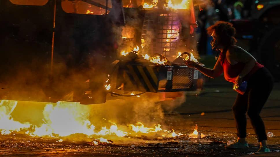 Кеноша, США. Протестующая подкуривает от мусоровоза, подожженного во время протестов в штате Висконсин