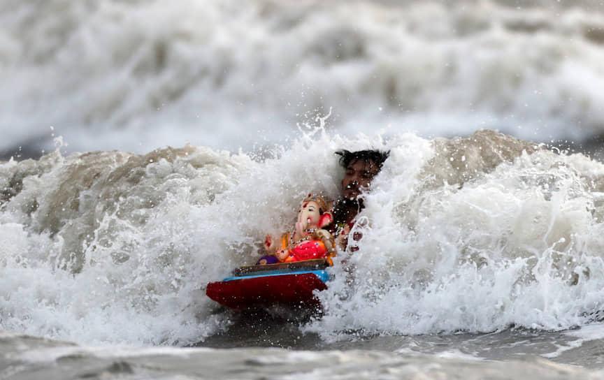 Мумбаи, Индия. Верующий купается с фигуркой бога Ганеши во время индуистского фестиваля