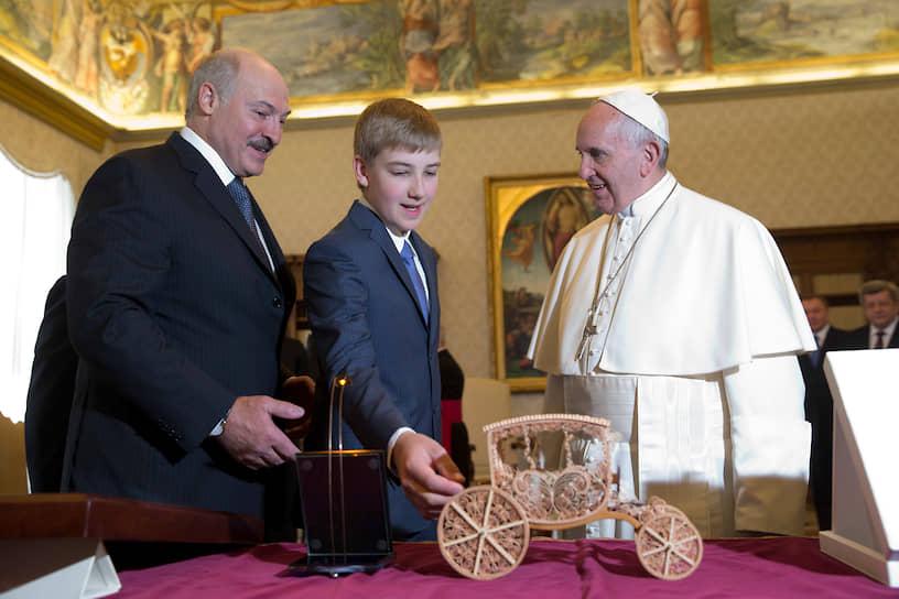 Папа римский Франциск обменивается подарками с президентом Белоруссии Александром Лукашенко и его сыном Николаем во время частной аудиенции в Ватикане, май 2016 года