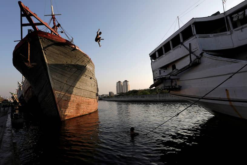 Джакарта, Индонезия. Мальчик прыгает в воду