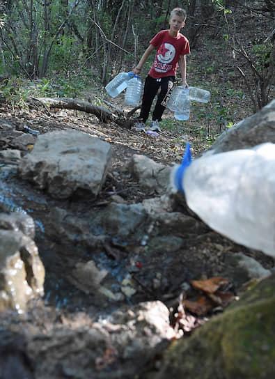 Село Верхняя Кутузовка, Крым. Местные жители набирают воду в горном роднике