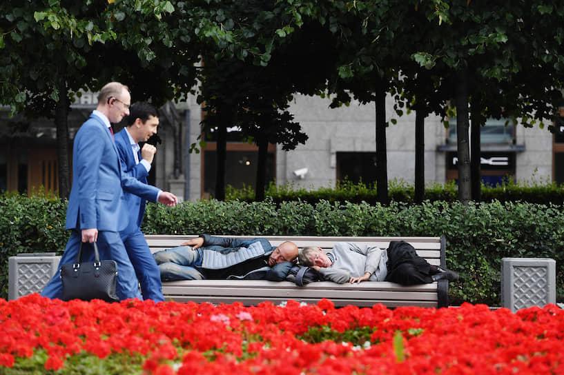 Москва, Россия. Мужчины в деловых костюмах проходят мимо лавочки со спящими людьми
