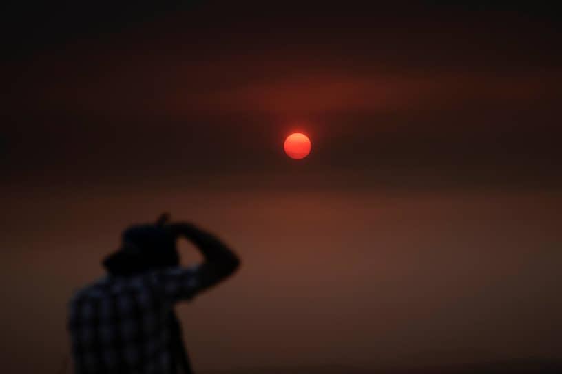 Вид на закат солнца через дым от пожаров