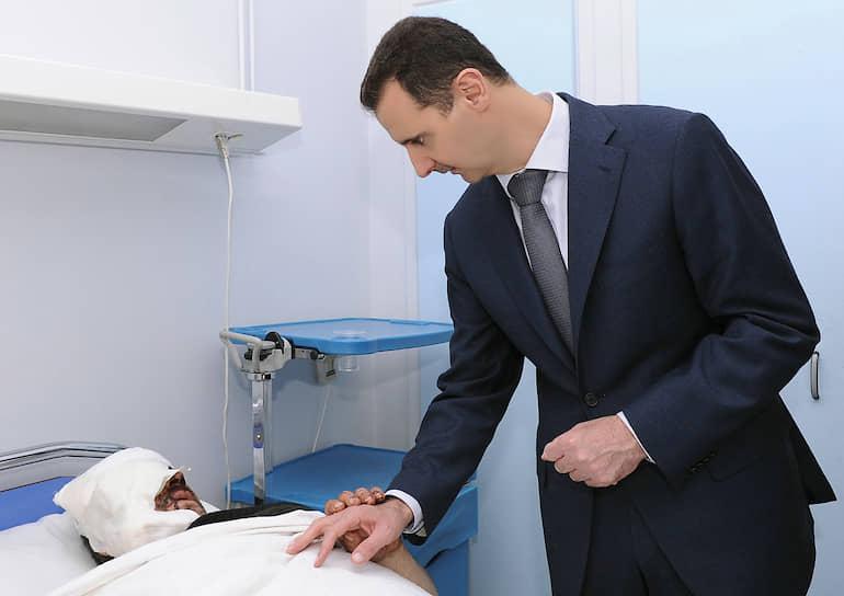Башар Асад частично пошел навстречу протестующим и отменил чрезвычайное положение, распустив правительство, однако затем при разгоне армией масштабных оппозиционных акций погибли сотни протестующих, столкновения переросли в гражданскую войну, жертвами которой к настоящему времени стали уже более 500 тыс. человек. После свидетельств правозащитников о массовых убийствах заключенных в правительственных тюрьмах западные лидеры стали называть Асада диктатором, президент обвинения отрицал<br> На фото: Башар Асад навещает в больнице солдат, раненных в столкновениях с оппозицией
