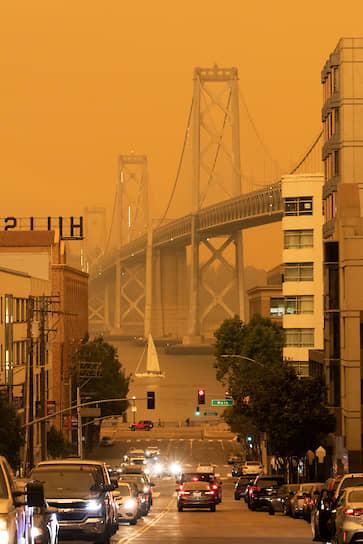 Мост Бей-Бридж между калифорнийскими городами Сан-Франциско и Окленд на фоне оранжевого неба
