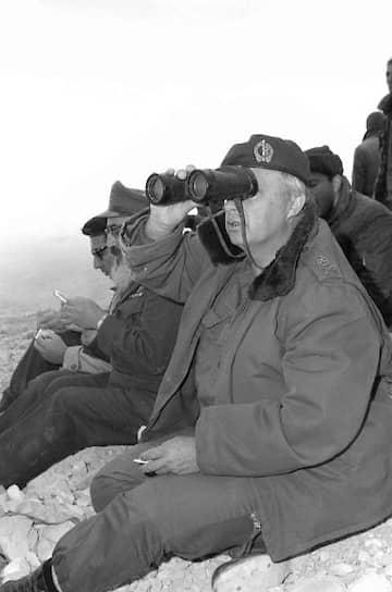 Командующий Южным военным округом Израиля Ариэль Шарон наблюдает в бинокль за ходом битвы в Караме с израильской стороны границы