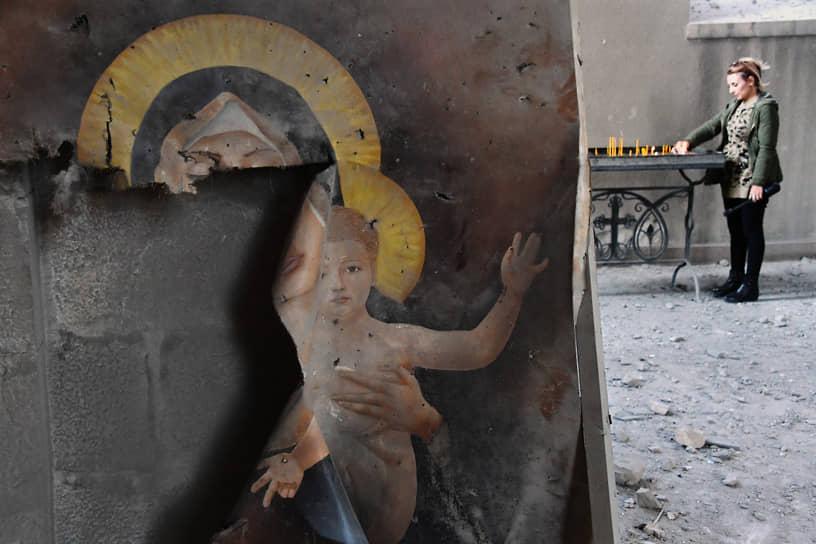 Женщина ставит свечку в соборе в городе Шуши (Нагорный Карабах), пострадавшем от обстрела