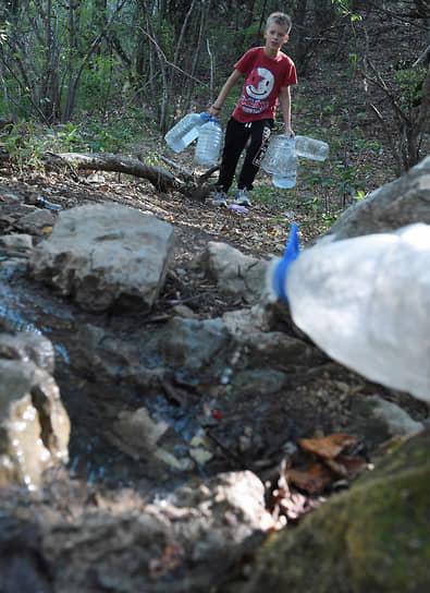 Из-за засухи в некоторых районах Крыма введены графики подачи воды.<br> На фото: мальчик с бутылками у родника
