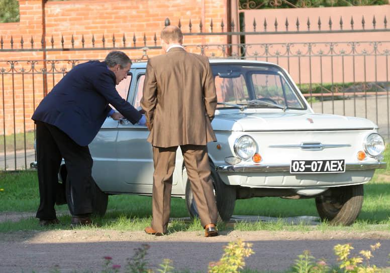"""Президент России <a href=""""/doc/4512541"""">Владимир Путин рассказывал</a>, что в молодости ездил на «Запорожце», который в 1972 году выиграла в лотерее его мама: «Дырка в глушителе образовалась, а денег на ремонт не было. Но правил не нарушали, хочу вам сказать. Правда, наверное, ездили без ремней безопасности. Да и ремней тогда не было» <br> На фото: Владимир Путин показывает президенту США Джорджу Бушу-младшему свой первый автомобиль на саммите G8 в Санкт-Петербурге в 2006 году"""